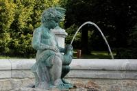 <p>  Okrogel kamnit bazen s figuro sedečega dečka z ribo, obdan s kamnitimi stebriči in bronastimi vazami. </p>  Foto: Luka Šparl